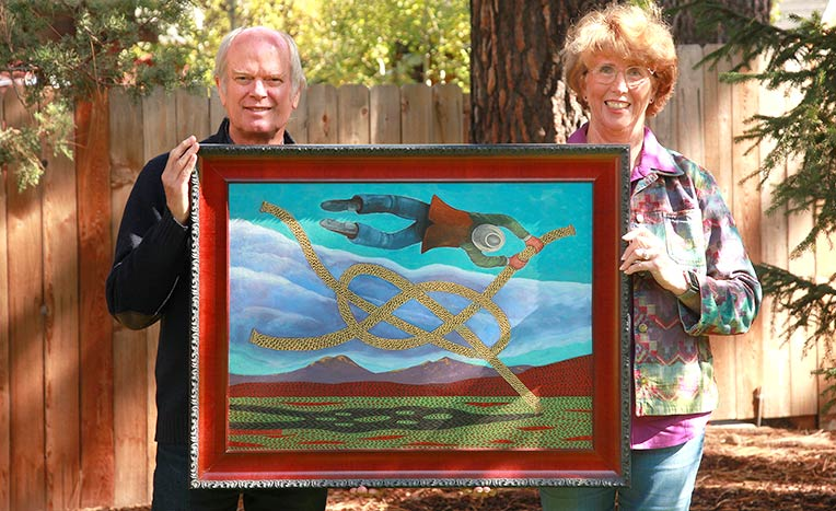 "Paul Bennett and Susan Emmons display Bennett's painting ""The Knot Rider."" wphoto provided"