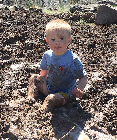 Three-year-old Talon van der Loon learns archery and gets his recommended daily allowance of muddy microbes in Sisters Country. photo provided